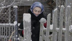 Uma menina em um lenço azul e com uma cesta no inverno sai da porta filme