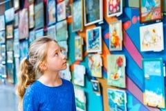 Uma menina em um museu em uma exposição de estudos belas artes das pinturas, pinturas de exame por autores famosos dos pintores fotografia de stock royalty free
