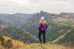 Uma menina em um revestimento lilás olha para fora na distância em uma montanha, em uma vista das montanhas e em uma floresta out Imagem de Stock Royalty Free