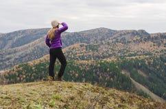 Uma menina em um revestimento lilás olha para fora na distância em uma montanha, em uma vista das montanhas e em uma floresta out Imagem de Stock