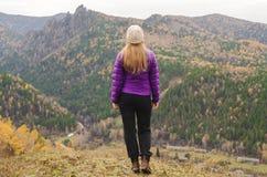 Uma menina em um revestimento lilás olha para fora na distância em uma montanha, em uma vista das montanhas e em uma floresta out Fotografia de Stock Royalty Free