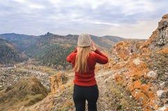 Uma menina em um revestimento vermelho olha para fora na distância em uma montanha, em uma vista das montanhas e em uma floresta  Fotos de Stock Royalty Free