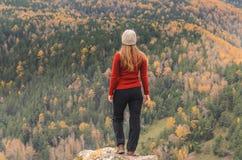 Uma menina em um revestimento vermelho olha para fora na distância em uma montanha, em uma vista das montanhas e em uma floresta  Imagens de Stock Royalty Free