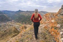 Uma menina em um revestimento vermelho olha para fora na distância em uma montanha, em uma vista das montanhas e em uma floresta  Fotografia de Stock
