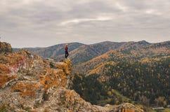 Uma menina em um revestimento vermelho olha para fora na distância em uma montanha, em uma vista das montanhas e em uma floresta  Imagens de Stock