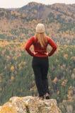 Uma menina em um revestimento vermelho olha para fora na distância em uma montanha, em uma vista das montanhas e em uma floresta  Imagem de Stock