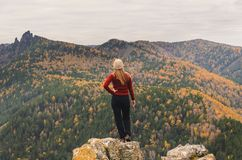 Uma menina em um revestimento vermelho olha para fora na distância em uma montanha, em uma vista das montanhas e em uma floresta  Fotografia de Stock Royalty Free