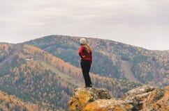 Uma menina em um revestimento vermelho olha para fora na distância em uma montanha, em uma vista das montanhas e em uma floresta  Fotos de Stock