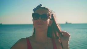 Uma menina em um roupa de banho de uma peça só vermelho e suportes dos vidros no litoral A menina toca em seu cabelo, fundindo no vídeos de arquivo