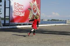 Uma menina em um tampão de guarnição militar corre ao longo da terraplenagem no fundo do bann Fotos de Stock