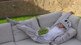 Uma menina em um terno da panda em um sofá que encontra-se para baixo comendo uvas video estoque