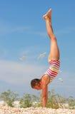Uma menina em um terno de banho listrado que está nas mãos Foto de Stock Royalty Free