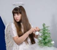 Uma menina em um traje do anjo decora uma árvore de Natal Imagem de Stock