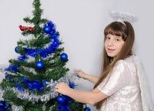 Uma menina em um traje do anjo decora uma árvore de Natal Fotografia de Stock