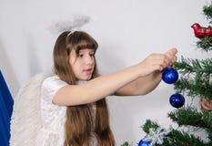 Uma menina em um traje do anjo decora a árvore de Natal Fotografia de Stock Royalty Free