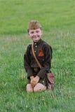 Uma menina em um uniforme militar que senta-se na grama na celebração de Victory Day em Volgograd Fotografia de Stock