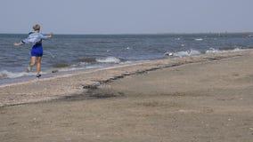 Uma menina em um vestido azul corre ao longo do litoral e dos sustos as gaivotas video estoque