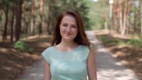 Uma menina em um vestido azul está andando no parque filme