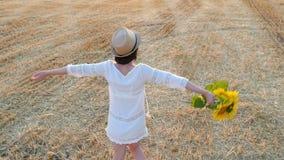 Uma menina em um vestido branco e em um chapéu de palha está guardando um ramalhete das flores de um girassol e está girando-o Jo video estoque