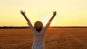 Uma menina em um vestido branco e em um chapéu de palha levanta suas mãos acima no campo de trigo durante o por do sol Uma jovem  vídeos de arquivo