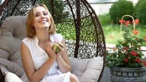 Uma menina em um vestido branco está comendo uma maçã verde filme
