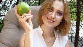 Uma menina em um vestido branco está comendo uma maçã verde video estoque