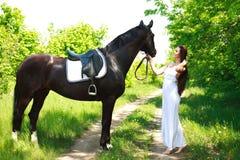 Uma menina em um vestido branco longo com um cavalo em uma estrada secundária Imagens de Stock