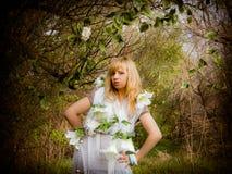Uma menina em um vestido branco nas madeiras com flores Imagens de Stock