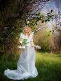 Uma menina em um vestido branco nas madeiras com flores Fotografia de Stock Royalty Free