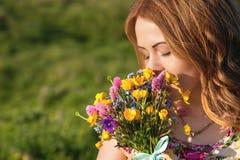 Uma menina em um vestido colorido guarda um ramalhete de flores selvagens fotografia de stock royalty free