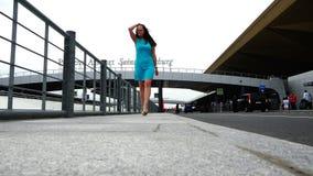 Uma menina em um vestido de turquesa está andando ao longo da plataforma do aeroporto vídeos de arquivo