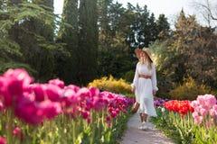 Uma menina em um vestido e em um chapéu brancos que anda no meio de um campo de tulipas multi-coloridas bonitas fotografia de stock