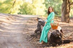 Uma menina em um vestido longo sentou-se para baixo para descansar em uma árvore caída fotografia de stock