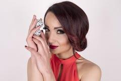 Uma menina em um vestido vermelho que guarda bolas do loto Fotos de Stock Royalty Free