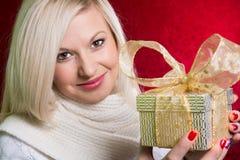 Uma menina em uma camiseta branca com uma curva do presente com vista enfaixada Imagem de Stock