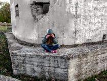 Uma menina em uma capa senta-se em uma pose dos lótus em um muro de cimento Fotos de Stock
