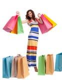 Uma menina em uma cor longa do vestido com sacos de compra Fotografia de Stock