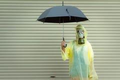 Uma menina em uma máscara de gás em um dia chuvoso fotos de stock royalty free
