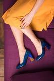 Uma menina em uma saia amarela e em umas sapatas azuis fotografia de stock