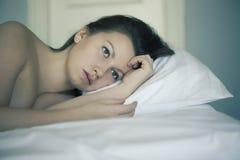 Uma menina encontra-se na cama pode o ` t cair pensamento e sonho adormecidos insomnia psychology Imagens de Stock Royalty Free