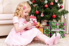 Uma menina está abrindo um presente Fotos de Stock Royalty Free