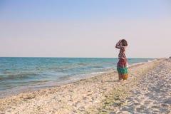 Uma menina está andando ao longo da praia Imagem de Stock Royalty Free