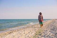 Uma menina está andando ao longo da praia Fotos de Stock Royalty Free
