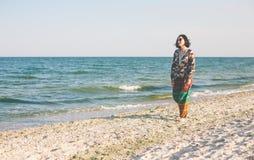 Uma menina está andando ao longo da praia Fotos de Stock
