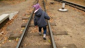 Uma menina está andando nos trilhos outono vídeos de arquivo