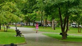 Uma menina está circundando um menino na chuva video estoque