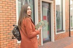 Uma menina está contra a construção na rua imagem de stock
