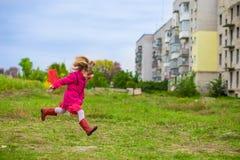 Uma menina está correndo com a rede da borboleta que tem o divertimento fotos de stock