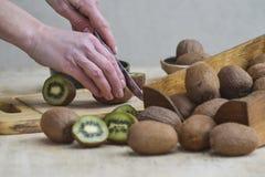 Uma menina está cortando o quivi maduro Demonstração do fruto fotografia de stock