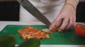 Uma menina está cozinhando uma salada na cozinha Corta o tomate suculento vermelho em muitas partes pequenas filme